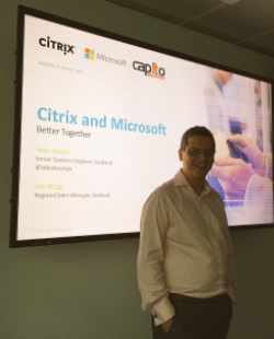 Toby Brown, Citrix, in front of large screen presenting at Capito Cloud event